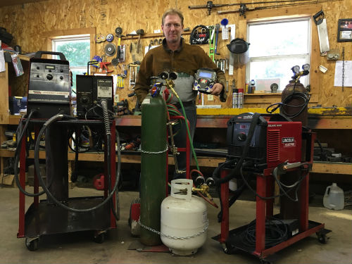 Me posing with my MIG and TIG welding carts that I built. I also modified a two-wheel dolly cart for my cutting torch.